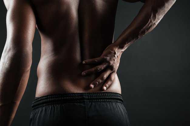 허리 통증으로 젊은 아프리카 계 미국인 남자의 자른 사진