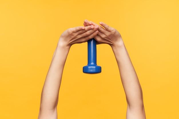 노란색 배경 위에 서있는 팔에 대한 excercises를 만드는 동안 그녀의 손을 유지하는 젊은 공정한 피부 여성의 자른 사진. 스포츠 및 바디 케어 개념