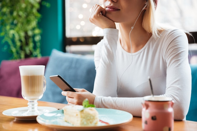 Подрезанное фото музыки молодой дамы слушая в кафе.