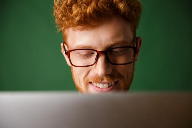 Обрезанное фото молодой readhead человек в очках, работая с ноутбуком