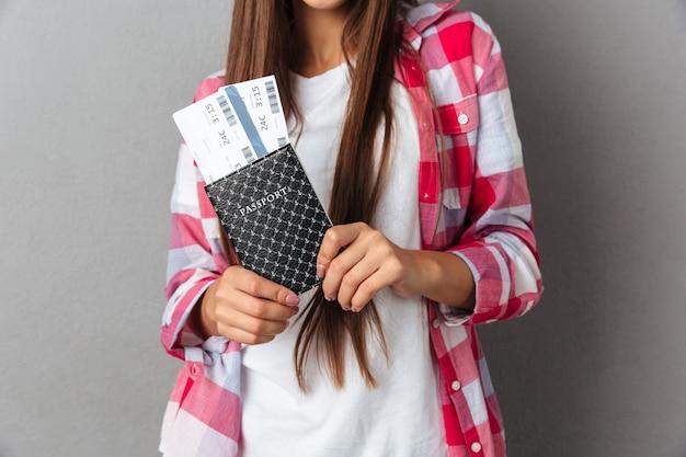 Подрезанное фото молодой женщины держа паспорт с билетами на самолет