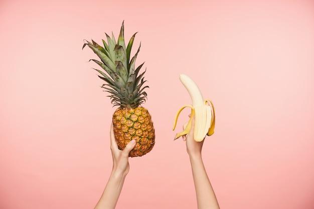 ピンクの背景で隔離されている間新鮮なパイナップルと皮をむいたバナナを保持している裸のマニキュアと若い女性の上げられた手のトリミングされた写真