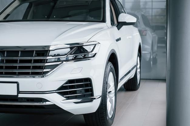 잘린 사진. 낮에 실내에 주차 된 현대적인 고급 흰색 자동차의 입자보기