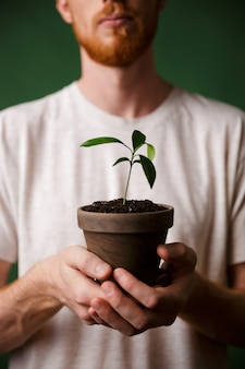Cropped photo of redhead bearded young man, holding potted plant