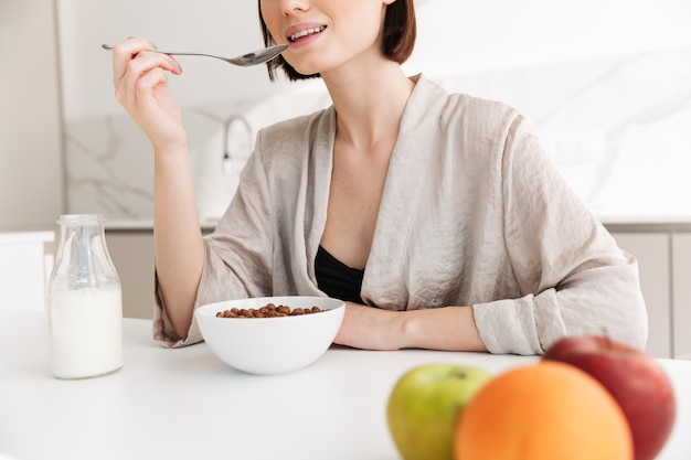 Cropped photo of satisfied woman 20s having breakfast in kitchen at home, and eating cocoa balls with milk
