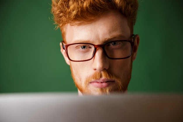 Cropped photo of serious young readhead man in glasses, working with laptop