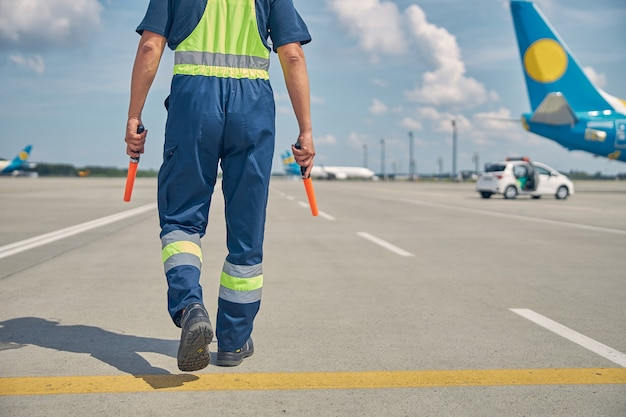 Cropped photo of a signalman with marshalling wands in his hands walking along the runway
