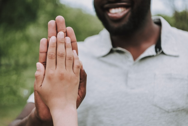 Cropped photo of son and dad give five each other