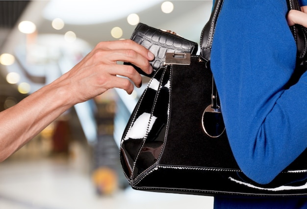 Cropped photo of thief stealing wallet from ladies' handbag, closeup