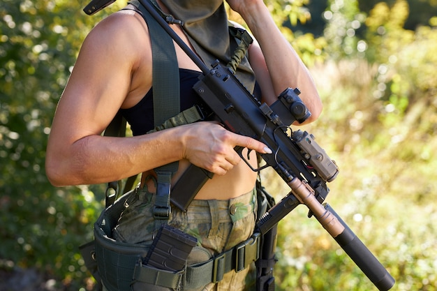 Cropped photo of unrecognizable woman holding rifle in hands