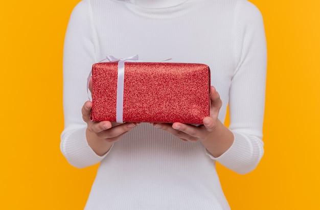 Foto ritagliata della donna che tiene un regalo nelle mani in piedi sopra il muro arancione