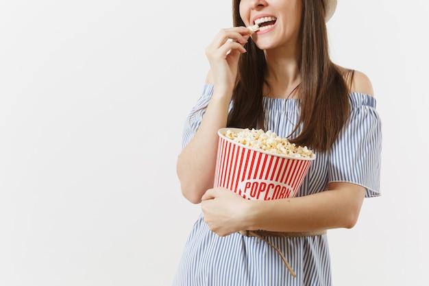 파란 드레스를 입은 자른 사진 여성, 흰색 배경에 격리된 양동이에서 팝콘을 먹는 영화 영화를 보는 모자. 사람들, 영화의 진지한 감정, 라이프 스타일 개념. 광고 영역입니다. 공간을 복사합니다.