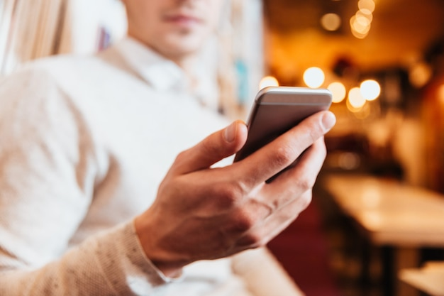 Cropped photo of young handsome man sitting in cafe while using mobile phone.