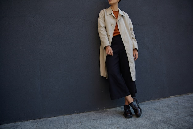 Cropped photo of young hipster woman dressed in black culottes, foxy sweater and beige trench, posing over black urban wall in trendy clothes and leather brogues
