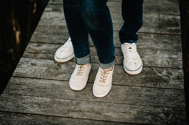 Cropped photo young legs in sneakers, married couple, husband and wife on a wooden bridge near lake. rear view of couple standing on pier. lower half.