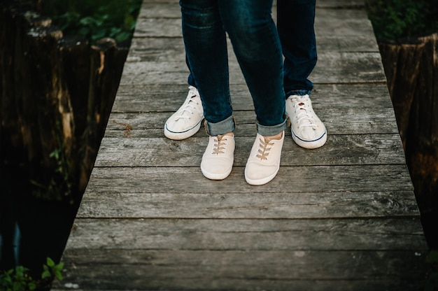 Cropped photo young legs in sneakers, married couple, husband and wife on a wooden bridge near lake