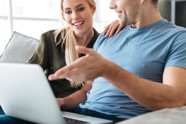 Cropped photo of young lovers using laptop computer on sofa