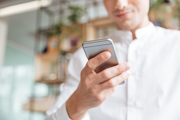 Cropped photo of young man dressed in white shirt using mobile phone. coworking.
