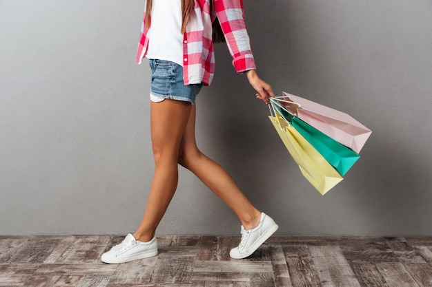 Cropped photo of young woman in casual wear holding shopping bags