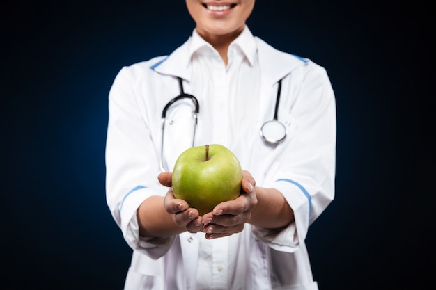 Cropped photo of young woman in medical gown holding green apple