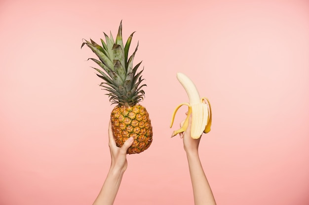 Cropped photo of young woman's raised hands with nude manicure holding fresh pineapple and peeled banana while being isolated over pink background