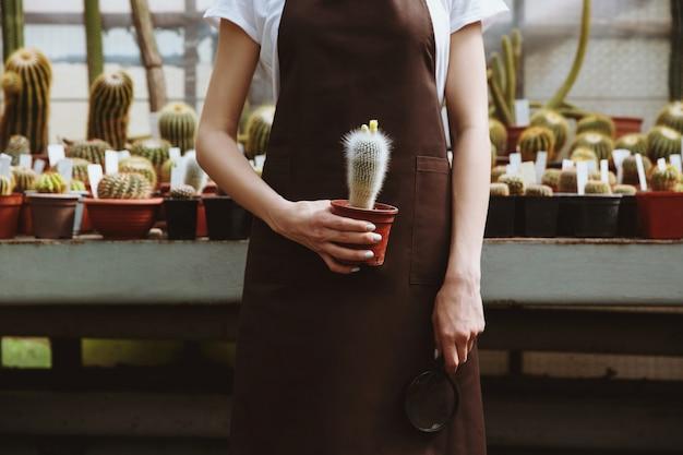 Foto potata della giovane donna che sta nella serra