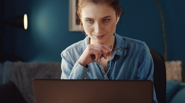 Cropped pic of young absorbed woman holding glasses looking at computer screen, front view