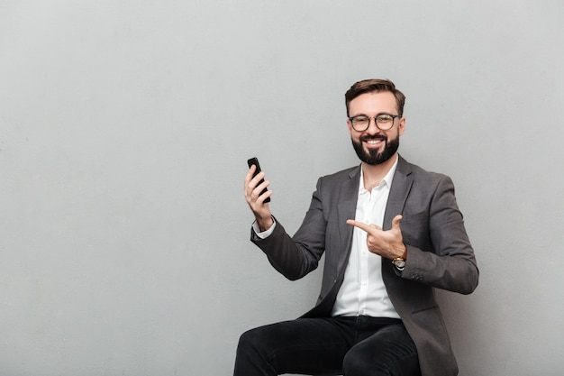 Cropped picture of happy man in eyeglasses looking on camera while sitting on chair and pointing on his mobile phone, isolated over gray