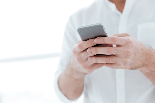 Cropped picture of man dressed in white shirt chatting by phone near big white window.