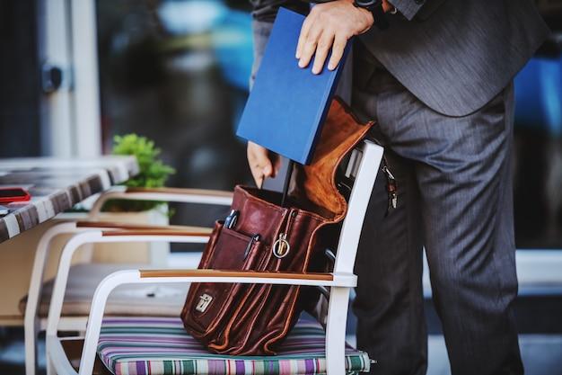 Обрезанное изображение элегантного бизнесмена в костюме, вынимающего повестку дня из кожаной сумки. внешний вид кафе.