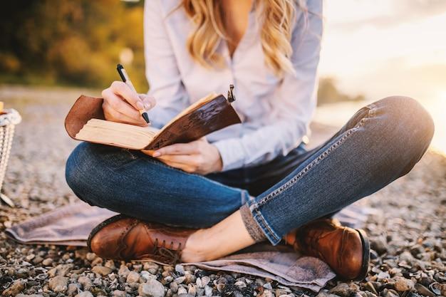 강 근처에 앉아서 노트북을 들고 집중된 유행 아름 다운 백인 여자의 자른 된 그림.