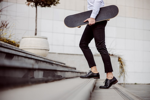 야외 계단을 오르고 겨드랑이 아래에서 스케이트 보드를 들고 셔츠에 잘 생긴 남자의 자른 그림.