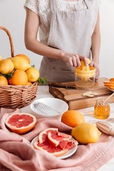 L'immagine ritagliata della donna spreme il succo di un agrume.