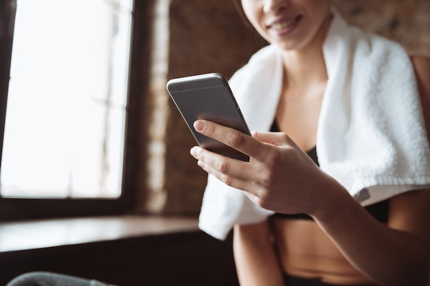 Cropped picture of young fitness woman chatting by phone.