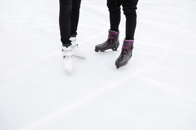 Cropped picture of young loving couple skating at ice rink