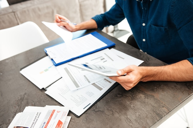 Cropped picture of young man's hands holding documents
