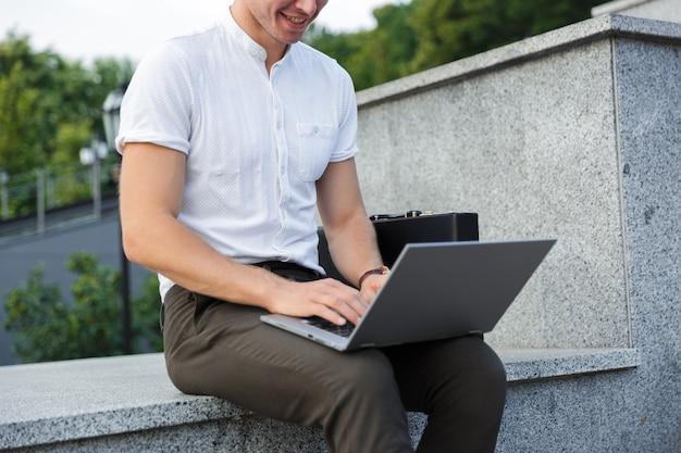 Обрезанный довольный деловой человек с портфелем, используя портативный компьютер, сидя на открытом воздухе