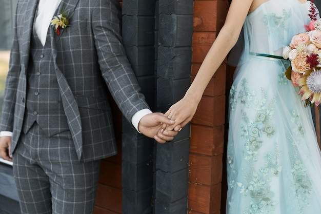 Cropped portrait of a handsome young man in checkered suit holding the hand of young woman in beige dress