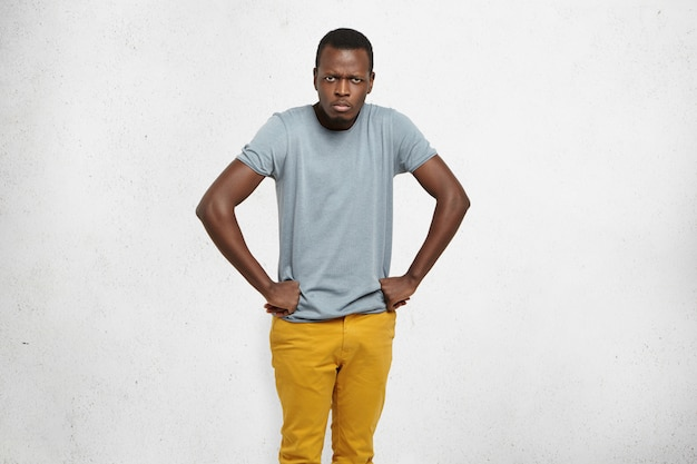 Cropped portrait of mad african american male wearing grey t-shirt and mustard jeans holding hands on hip, frowning, having grumpy angry look, dissatisfied with misbehavior of his little children