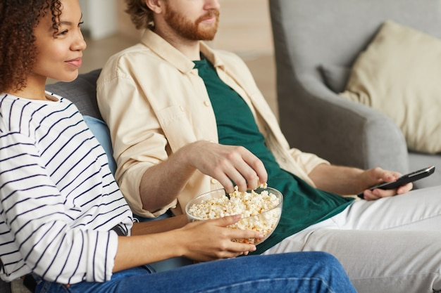 Cropped portrait of modern mixed-race couple watching tv at home while relaxing on cozy sofa, focus on hands holding bowl of popcorn