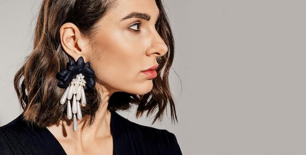 프로필에 큰 귀걸이를 가진 여자의 자른 초상화