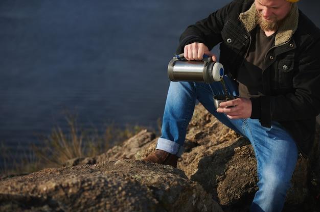 Обрезанный портрет авантюриста, сидящего на скалах с термосом, наливающего в чашку теплого напитка и отдыхающего во время прогулки на природе