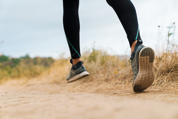 해변에서 운동하는 동안 달리는 운동복을 입은 운동 여자의 자른 초상화