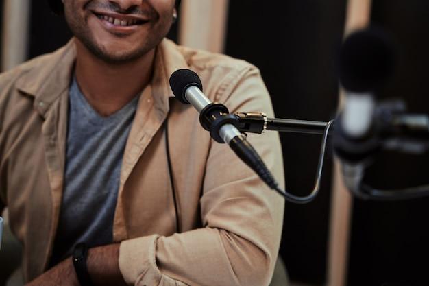 방송에서 말하는 동안 카메라를 보며 웃고 있는 행복한 젊은 남성 라디오 진행자의 자른 초상화
