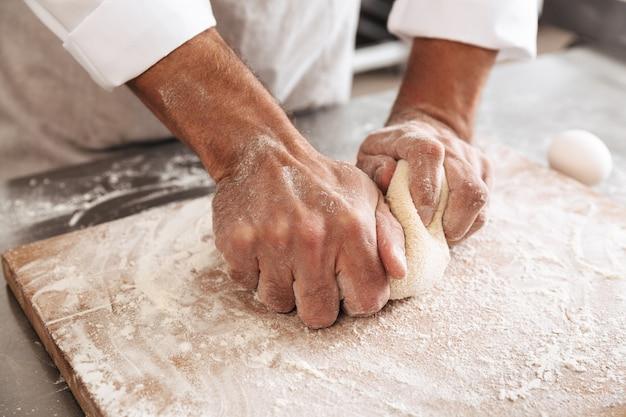빵집이나 부엌에서 테이블에 빵 반죽을 만드는 남자 수석의 자른 초상화