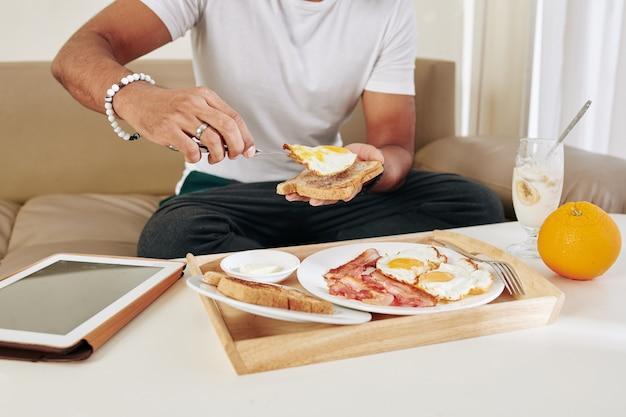 Обрезанный портрет человека, едящего тост с жареным яйцом и беконом на завтрак