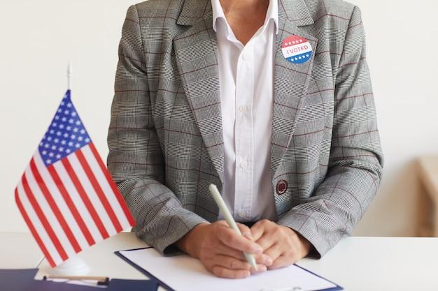 Обрезанный портрет зрелой женщины, сидящей за столом с американским флагом на избирательном участке в день выборов и регистрирующейся для голосования