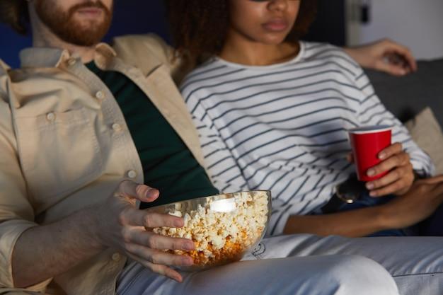 Обрезанный портрет современной пары смешанной расы, смотрящей фильм во время свидания в кинотеатре