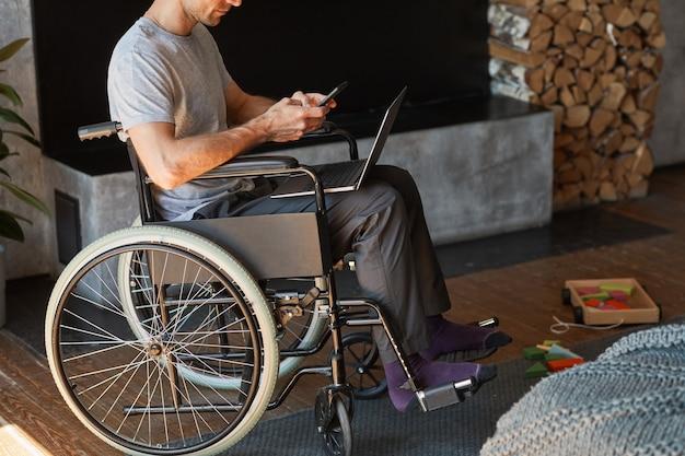 車椅子に座っている間、自宅でラップトップを使用して、障害を持つ現代人のトリミングされた肖像画、コピースペース