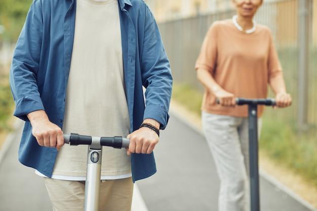 Обрезанный портрет современной пожилой пары, катающейся на электрических скутерах на открытом воздухе в красивой городской обстановке, копией пространства